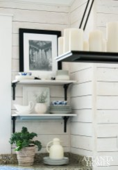 The kitchen's pine-plank walls convey a casual attitude, as do the open shelving and sconces from Restoration Hardware. Brown's wife took the black-and-white photographs while on vacation in San Francisco.