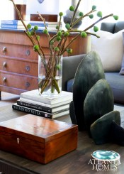 """On the sunroom coffee table, an antique wooden box is placed next to a striking abstract sculpture from Oly Studio. Describing his personal design philosophy, Brown notes, """"I don't like things that are overly designed. Simple simplicity is what I do best."""""""