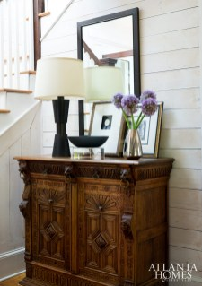 The entry hall introduces visitors to Brown's skillful mix of new and old pieces, including a carved oak chest that the designer's father bought at auction long ago.