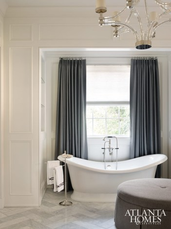 A luxurious Vandabath soaking tub serves as the focal point in the spa-like master bath. It's complemented by sparkling accents such as the chandelier from Circa Lighting. Cabinetry, Block & Chisel. Ottoman, custom by Douglass Workroom. Tile, Traditions in Tile.
