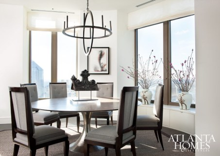 A round Julian Chichester dining table, available at Holland & Company, and Noir's Montel metal chandelier echo the curved walls of the residence's dining area. The 1940s-era French Modern chairs are upholstered in a Holland & Sherry grey wool.