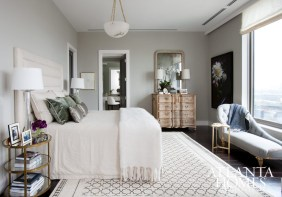 "Westbrook based the master bedroom's cream, grey, and lavender color palette on hues found in Whitney Ott's floral photograph, which is positioned alongside an antique French wooden chest. The designer notes that most of the home's antiques ""have a Continental feel to them."""