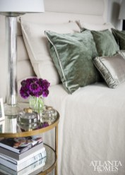 The bed pillows' lustrous fabric and a posy of purple anemones accent the room's hushed tones.