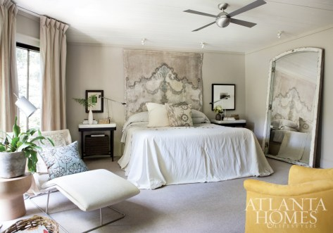 The master bedroom exudes European luxury with its interesting mix of periods, colors and styles. Improvisation—in the form of a custom tapestry headboard and a pair of antique linens sewn together to make a coverlet—is further evidence of the creative energy and joie de vivre that pervades the house.