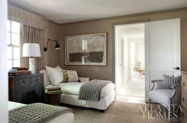The master suite leads to a third sleeping spot repurposed as a cozy, cocooning den. In this sumptuous lounge area, boxed valances covered in Kelly Wearstler fabric help the TV-watching space feel more contained, while the walls' diamond-weave Phillip Jeffries grasscloth lends a handsome, textural effect. The framed artwork is by Helen Durant, an artist the Tilinskis discovered at The Goat Farm years ago. The alabaster lamp is by Visual Comfort.