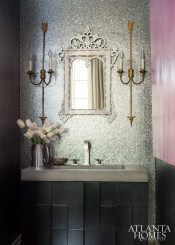 The main level's elegant powder room stays on point with golden arrow sconces from Parc Monceau Antiques.