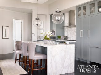 A pair of playful lanterns tops the island of Calacatta Gold marble, while dark gray cabinets keep clutter out of sight, with glass display space on top.