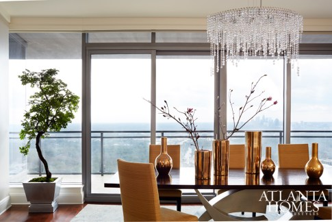 A sculptural table by Henry Royer serves as the dining room's centerpiece. Rudin dining chairs featuring a textured Robert Allen fabric complement the table's clean lines. The prism chandelier by Schonbek Lighting was hung closer to the ceiling to showcase views of the Buckhead skyline.