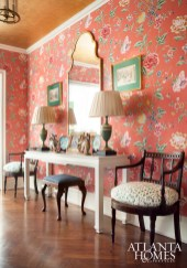 Bold rose-colored floral wallpaper sets the tone in the foyer, where a gilt mirror and white lacquered console from Parc Monceau are paired with English Regency armchairs.