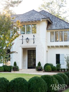 The façade of this Peachtree Park abode belies its 9,000-square-foot size. The architectural aesthetic favors a contemporary coastal style, using natural elements like limestone, painted brick and iron. Limestone surrounds from Materials Marketing. Stone from Stone Center.