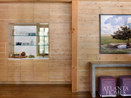 Douglas fir tongue-and-groove planks cover the walls seamlessly for a contemporary twist to rustic style. Lugo ottomans upholstered in purple de Le Cuona linen nestle under the waterfall concrete console by John Ziebarth for overflow seating.