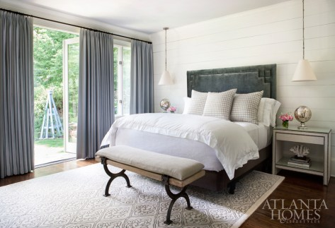 In a guest suite, French doors open onto a hillside garden with layers of blooming beds. The hanging lamps are Circa; the hearty Atlas bench is from Arteriors, and the linen curtains are Norbar.