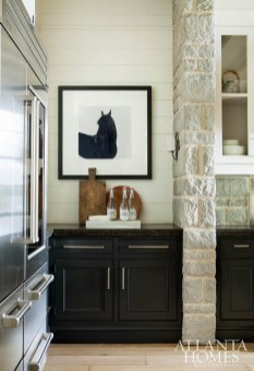 Spitzmiller and Norris compare their custom stone niche around the stove and hood to a hearth, appropriate given the homeowners' propensity for entertaining family and friends in the space. Cabinetry by Ramey's Custom Cabinets. The stools are Noir, pendant lights are Urban Electric and artwork is from Stanton Home Furnishings.