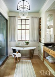 A Waterworks tub in the master bath creates a stunning focal point. Its classic charm is complemented by custom window treatments fabricated by Willard Pitt Curtain Makers. Lighting is from Urban Electric and the runner is Dash & Albert.