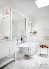 A custom oversize mirror in the master bath helps flood the windowless space with natural light from the new skylight.