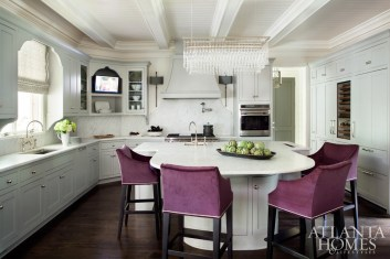 Eggplant-hued barstools bring liveliness to the soft gray kitchen. The oversized ceiling fixture, from R Hughes and appropriately named Light Drizzle, dresses up the space with rows of sparkling lights.