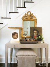 An antique mirror and portrait sourced from the South of France take pride of place in the foyer.