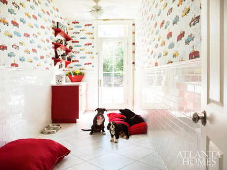 In the dogs' area, subway tiles and a floor drain make easy work of cleaning up messes; a Tyler Hall wallpaper of dogs driving convertibles adds a dose of fun.