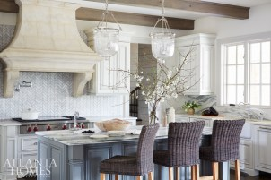 The kitchenjuxtaposes varying textures rather than contrasting colors. The Carrara marble backsplash—laid in a herringbone pattern next to the stone hood, wooden beamed ceiling, and veiny Vermont marble countertops—brings a soft, subtle contrast to the space.