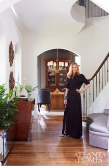 Shayelyn stands in the foyer of her home near a custom console from Bradley.