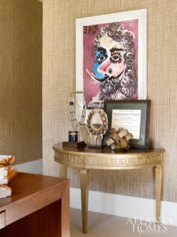 A prized lithograph by Pablo Picasso is displayed among other objets d'art on a Mr. Brown demuline. A grasscloth wallcovering by Phillip Jeffries delivers polished ambience in the study.