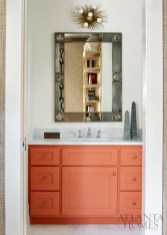 In the adjoining bathroom, a pop of orange provides dimension.