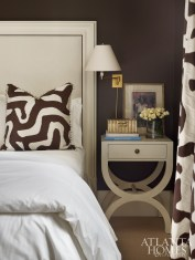 A bold Jed Johnson fabric from Travis & Company in the guest bedroom echoes the rich brown walls. The heaboard is Century; the nighstand is Tritter Feefer.
