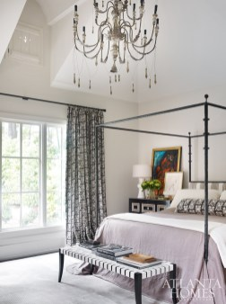 The master bedroom effortlessly mixes traditional and modern styles. The custom bed is by Ironware International; the Neidermaier bench is from Travis & Company.