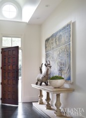 The entry foyer features an antique carved deer from Bali.