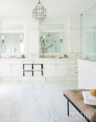 The master bathroom was inspired by a photograph of an all-white, marble-clad bath that McKenzie loved; the Art Deco–style sconces are a nod to the architecture.