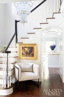 The entry of this Peachtree Battle abode serves as a calming counterpoint to the boisterous spaces beyond, with pale gray walls (Benjamin Moore's Pale Oak) and a shiplap-sided banister.