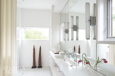 """The bath is actually quite small and irregularly shaped, so we kept everything white,"" notes Musso. Sleek cabinetry by Design Galleria Kitchen and Bath Studio and geometric lighting from Tech Lighting reflect the home's modern verve, while a pair of wooden sculptures add warmth."