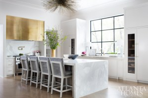This freshly renovated kitchen showcases a masterful mix of materials. The cabinets are by Stile Inc. Fine Cabinetry and hardware by DLV Designs. The brass hood is by Grey Furniture, and the stools are by Björk Studio.