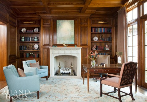The homeowners relax in the library most evenings. The matching Baker club chairs sit across from the Holland & Company desk in the walnut-covered room. A painting by Amy Sullivan, represented by Huff-Harrington Fine Art Gallery, hangs above the mantel.
