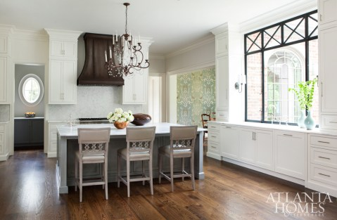 The kitchen, co-designed by Cynthia Ziegler, mixes formal touches, like the beautiful Niermann Weeks chandelier, with warm elements, like a Moulthrop bowl crafted from a walnut tree on the property. Various metals mingle throughout the space, like the eye-catching metallic finish on the Hickory Chair counter stools, the aged-copper hood and the polished-nickel plumbing.