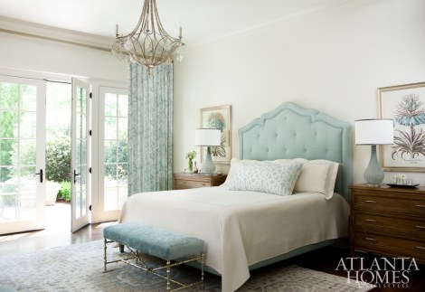A custom tufted headboard by Huff-Dewberry sets the stage for the cool and tranquil bedroom, where Elizabeth Hamilton curtains and a Kravet-covered bench from Oly Studio rein in the blues. Bedside botanical prints from Peridot and lamps from Bungalow Classic keep with the room's coastal cues.