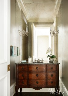 The main floor powder room boasts antique mirrors and a silver stria-technique glaze on the side walls, adding subtle glamour while opening up the room.