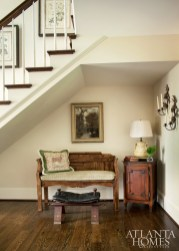 """A cozy nook in the foyer also features time-honed treasures, such as an old bench, a French table and a petite leather stool that has served as the """"time-out stool"""" for many generations."""