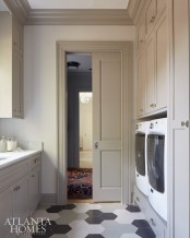 """""""With a little bit of effort, you can make laundry rooms interesting and fun,"""" says Howard. Here, a custom floor pattern with tiles from Design Works Marble Shop adds graphic interest."""