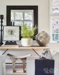 A rustic-chic focal point in the living room includes an antique trestle table, an iron stand and candelabra from Townhouse by Robert Brown and pottery from B.D. Jeffries.
