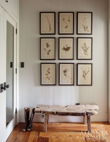 A series of botanicals from Holland & Company hang above a bench from B.D. Jeffries near the master closet.