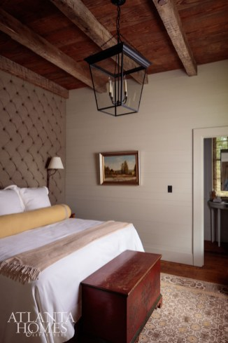 A shotgun shell button-tufted upholstered wall adds interest to a main-floor guest bedroom.