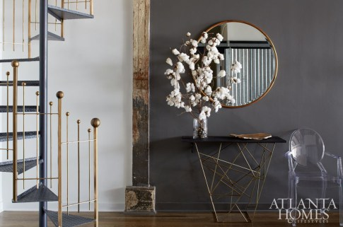 A mix of metals help soften the industrial vibe in designer Minhnuyet Hardy's Atlanta loft. She refreshed the original staircase by painting the railing a glimmering gold.
