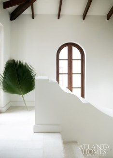 A palm frond adds interest to the stair hall, painted Benjamin Moore's China White.