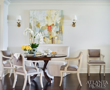 left In the dining area, a custom banquette and Holland & Company dining chairs cradle a New Classics table, facilitating the movement of traffic to the living room and kitchen. The abstract artwork is by Stephanie Wheeler through Webb Marsteller.