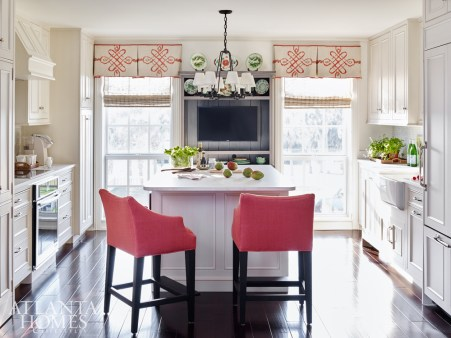 Watermelon red adds oomph to a pair of linen-covered counter stools in the kitchen, which was completely redone with the help of a local contractor. The sophisticated scroll pattern on the valances comes from an Osborne & Little fabric, beautifully flanking a small collection of the homeowners' own colorful pottery.