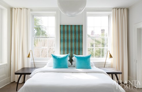 The master bedroom reflects Kay's efforts to keep everything as light and airy as possible. Even a low headboard would have blocked the windows to King Street, so she devised the blue-and-green velvet panel, which adds a wow factor while anchoring the king-size sleeping spot.