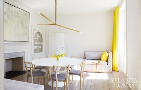 """When designer Kay Douglass and her husband, Jim, purchased a classic Charleston Single House in January 2016, the designer knew she wanted to give it a modern Parisian flair, and the dining room is perhaps the best example of this aesthetic. """"I love the reflection of the chandelier in the mottled-glass mirror over the fireplace,"""" Kay says. """"It's magical day and night."""""""
