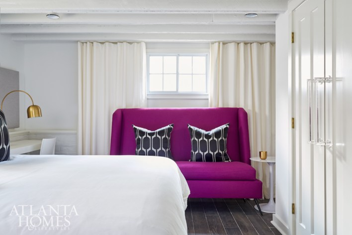 The terrace-level guest room features a magenta sofa from S.O.M. and closets accessorized with oversize acrylic handles that Kay cleverly fashioned from CB2 towel bars.