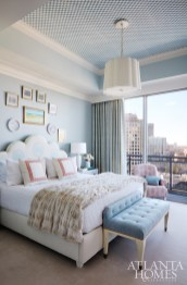 The master bedroom's atmosphere has hints of glamour that spring from the velvet coverlet, faux-fur throw and custom wallpaper on the ceiling by Stephen Floyd Design.